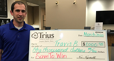Travis and big check for $1,000