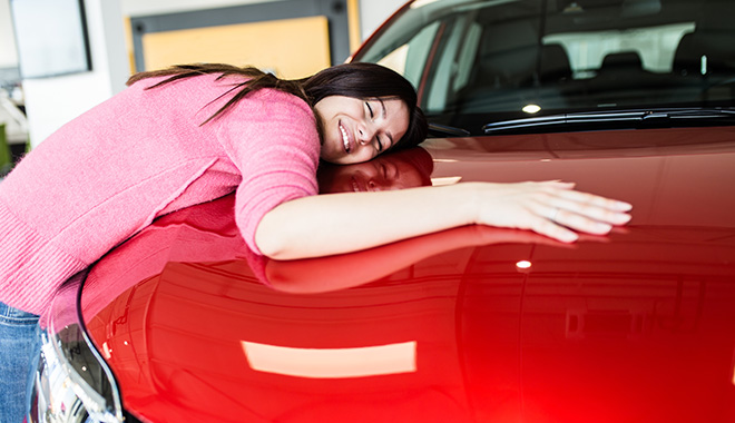Girl hugging red car