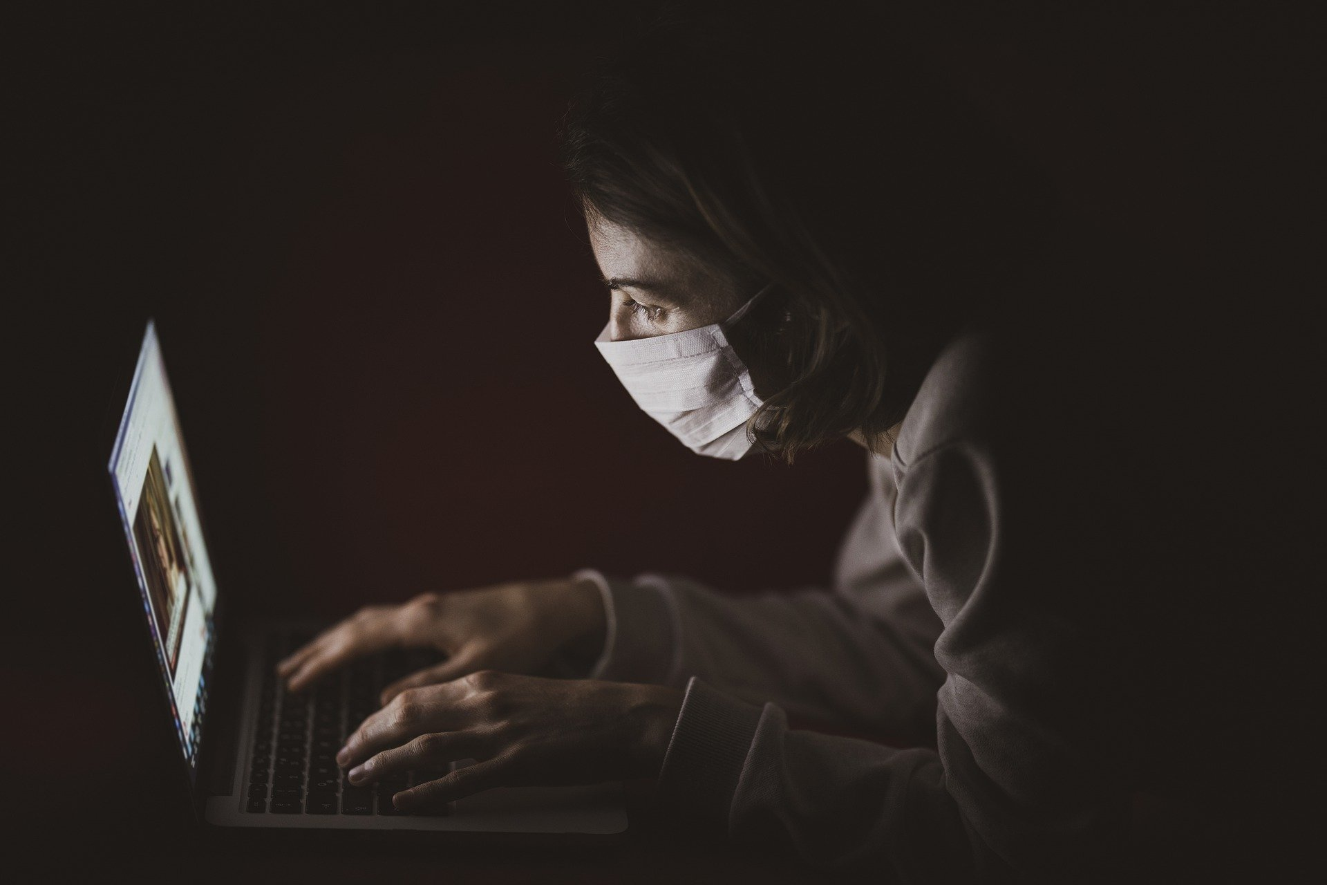 masked person in the dark on a computer