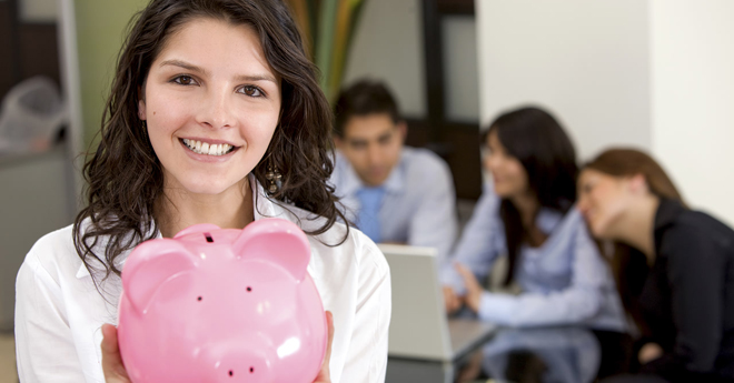 Person holding out a pink ceramic piggy bank with three more people in the background looking at a laptop computer.