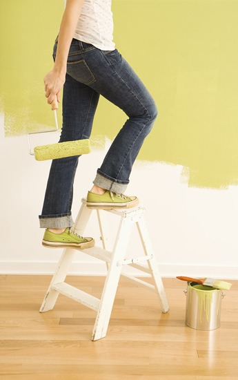 Person climbing a short step ladder about to paint a wall lime green.