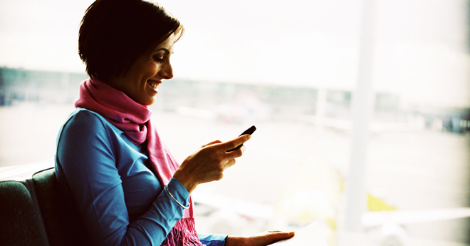 Person sitting, smiling and looking at a mobile phone.