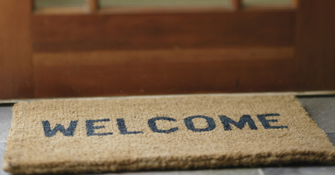 Coir fiber door mat in front of a door with the word welcome printed on the mat.
