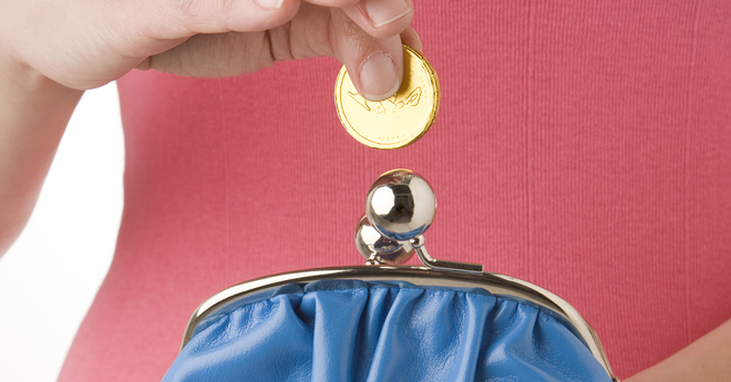 Hands holding a blue coin purse about to drop a gold coin into the purse,