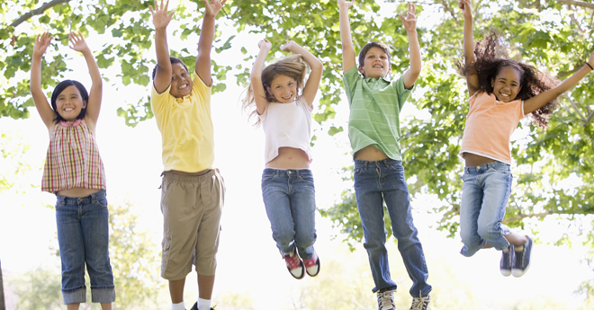 Kids jumping into the air with their arms above their heads laughing.